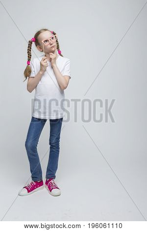 Full Length Portrait of Thinking Caucasian Blond Girl With Pigtails Posing with Artistic Spectacles Against White Background. Vertical Image Composition