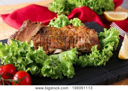 Yummy grilled spare ribs with fresh salad leaves on black board