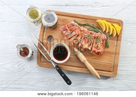 Raw pork ribs and ingredients for cooking on wooden table