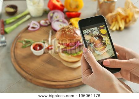 Female hands taking photo of food with mobile phone