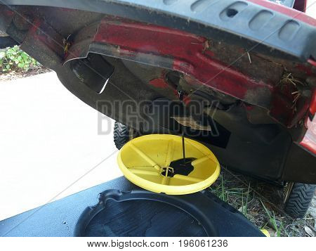 Close-up of oil draining into a yellow and black container during an oil change on a red lawn mower.