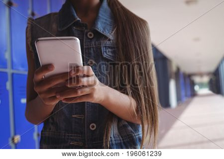 Elementary student using smartphone while standing in corridor at school