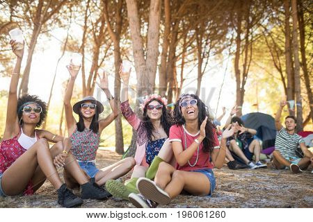Cheerful friends enjoying together while sitting on field at campsite