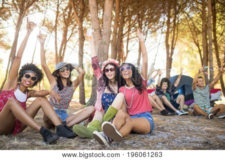Cheerful friends with arm raised sitting together on field at campsite