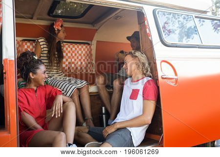 Happy young friends sitting together in camper van