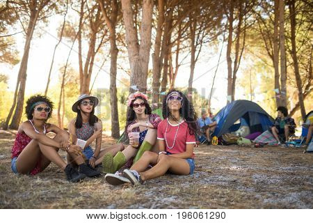 Young female friends sitting together on field at campsite