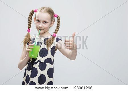 Portrait Of Cute And smiling Caucasian LIttle Girl With Pigtails Posing in Polka Dot Dress with Cup of Greeen Juice. Drinking Through Straw. Showing Thumbs Up Sign. Horizontal Image