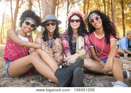 Portrait of happy female friends sitting together on field at campsite