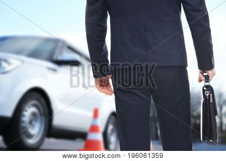 Insurance agent with briefcase and car on background