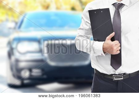 Insurance agent with clipboard and car on background