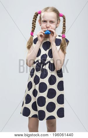 Portrait of Funny Caucasian Blond Girl With Pigtails Posing in Polka Dot Dress Against White. Blowing Up Blue Air Balloon.Vertical Image