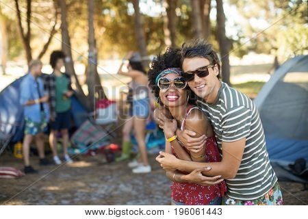 Portrait of smiling young friends embracing at campsite