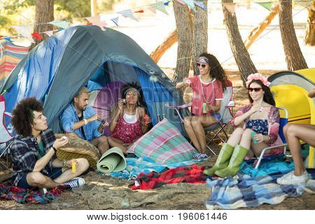 Happy young friends enjoying by tents on field at campsite