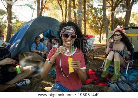 Smiling young woman holding bubble wand with friends in background at campsite