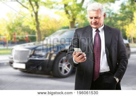 Insurance agent using smartphone and car on background