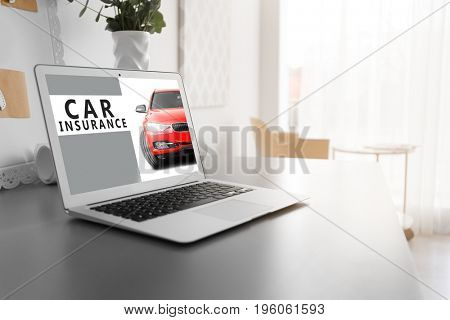 Modern laptop on table at home. Car insurance concept