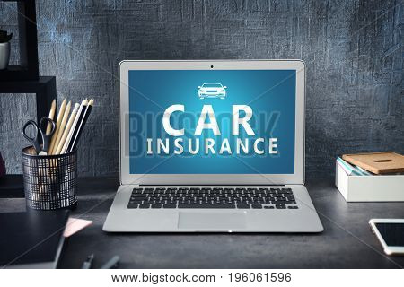 Modern laptop on table in office. Car insurance concept