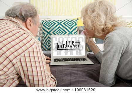 Senior couple using laptop at home. Life insurance concept