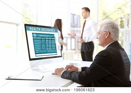 Senior man working with computer in office. Health insurance concept
