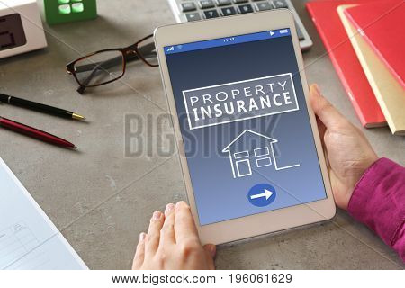 Woman using tablet in office. Property insurance concept
