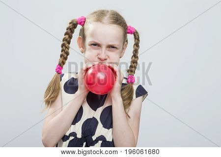 Portrait of Funny Caucasian Blond Girl With Pigtails Posing in Polka Dot Dress Against White. Blowing Up Red Heart Shaped Air Balloon. Horizontal Image