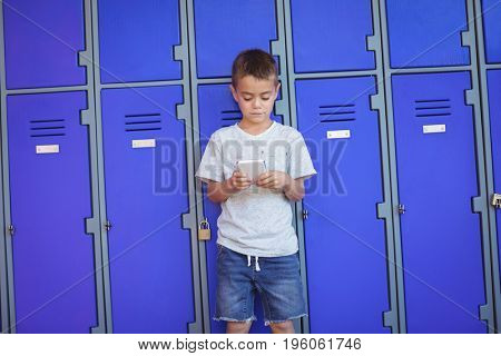 Boy using mobile phone while standing against lockers at school