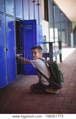 Portrait of boy taking books from locker at school corridor