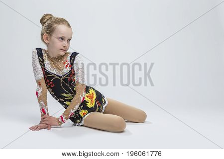 Sport Ideas. Young Caucasian Female Rhythmic Gymnast Athlete In Professional Competitive Suit Posing in Studio Against White.Horizontal Image