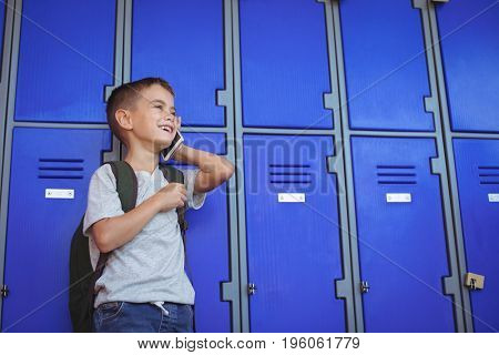 Happy boy talking on mobile phone while standing against lockers at school