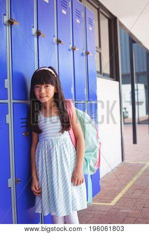 Portrait of elementary girl standing by lockers in corridor at school