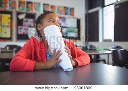 Thoughtful girl covering face with papers while sitting at desk in classroom