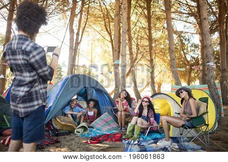 Man photographing smiling friends by tents at campsite