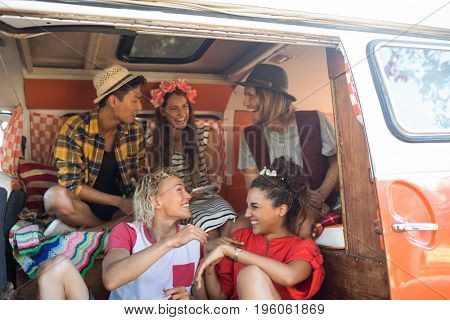 Cheerful young friends sitting together in camper van