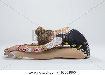 Sport Ideas. Young Caucasian Female Rhythmic Gymnast Athlete In Professional Competitive Suit Doing Backbend Stretching Exercise While Posing in Studio Against White. Horizontal Image