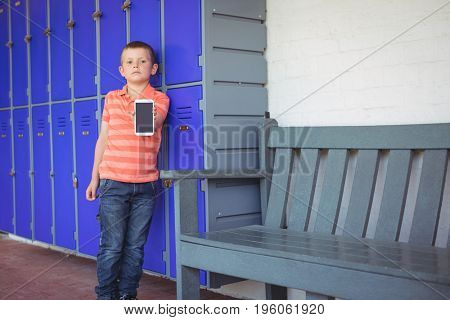 Portrait of boy showing mobile phone while leaning on lockers in corridor at school