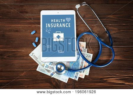 Tablet, money and stethoscope on wooden background. Health insurance concept
