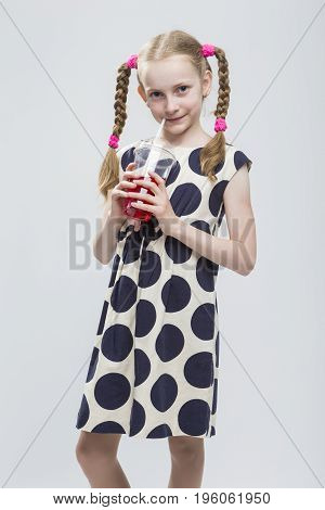 Kids Concepts. Portrait of Beautiful Caucasian Blond Girl With Pigtails Posing in Polka Dot Dress Against White. Holding Cup with Red Juice and Straw. Vertical Image