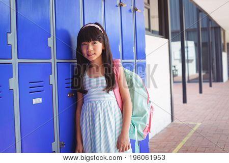 Portrait of elementary schoolgirl standing by lockers in corridor at school
