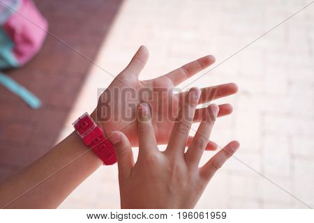 Cropped hands of student in corridor at school during sunny day