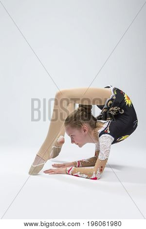Sport Ideas. Young Caucasian Female Rhythmic Gymnast Athlete In Professional Competitive Suit Doing Backbend Stretching Exercise While Posing in Studio Against White. Vertical Image Orientation