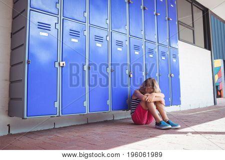 Full length of schoolgirl sitting on pavement by lockers in corridor at school