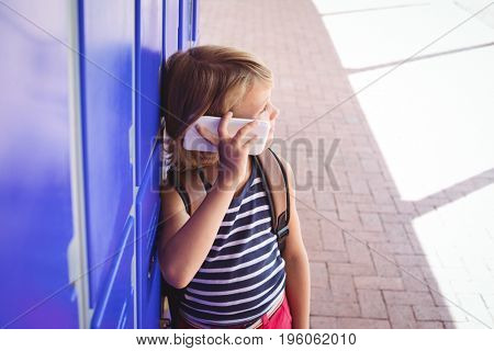Schoolboy talking on mobile phone while standing by lockers in corridor at school during sunny day
