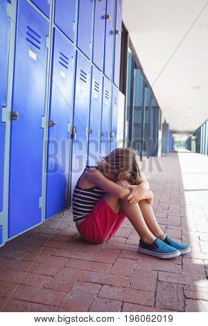 Full length of girl sitting on pavement by lockers in corridor at school