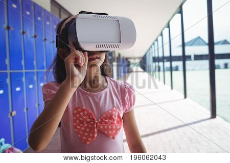Elementary student using virtual reality glasses while standing in corridor at school