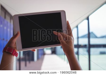 Cropped hands of student using digital tablet in corridor at school
