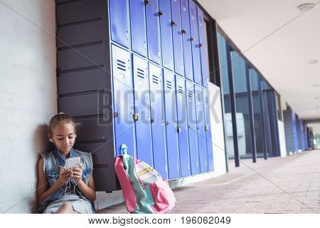 Elementary schoolgirl listening music through headphones while using mobile phone by lockers at school
