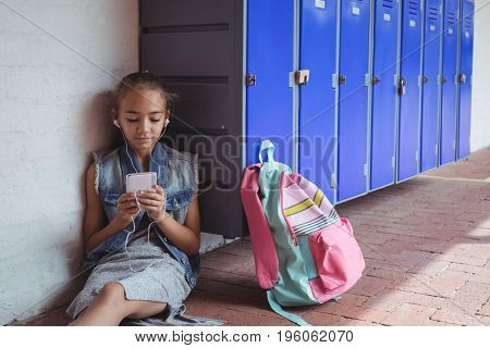 Elementary student listening music through headphones while using mobile phone by lockers at school
