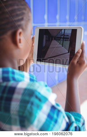 Schoolboy photographing corridor through digital tablet while standing at school during sunny day