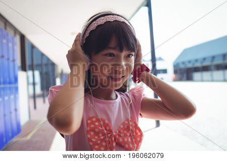 Smiling girl listening music through headphones while standing in corridor at school