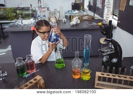 High angle view of elementary student examining blue chemical in flask by desk at science laboratory